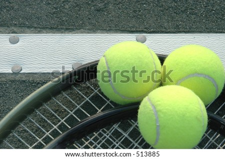 three balls two racquets on the tennis tape