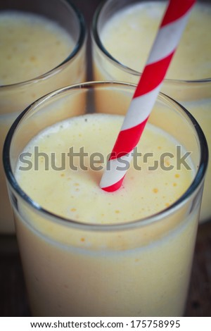 Three banana smoothies with a striped red straw  - stock photo