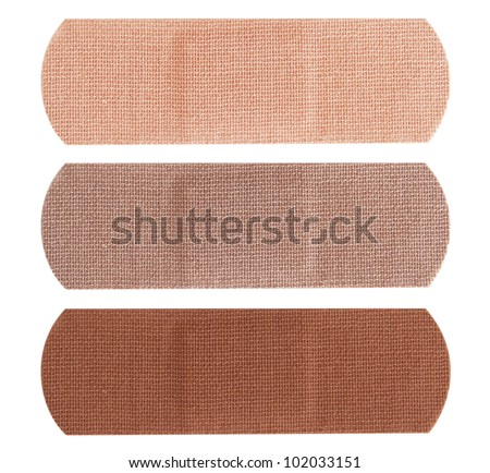 Three bandages in different skin colors isolated on white background. - stock photo