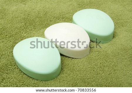 Three bars of soap on the green bath towel