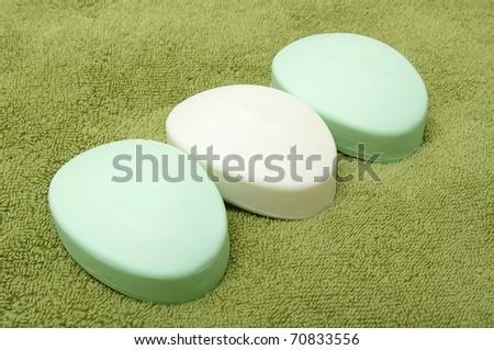 Three bars of soap on the green bath towel - stock photo