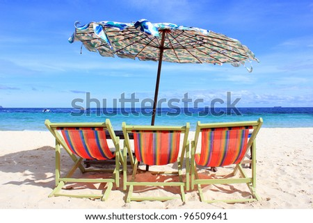 Three beach chairs with old umbrella and beautiful beach on a sunny day