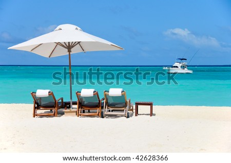 three beach chairs with white umbrella and yacht at ocean front - stock photo