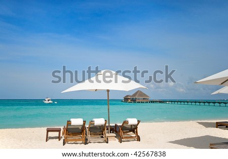 three beach chairs with white umbrella at ocean front - stock photo