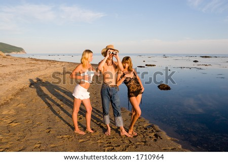 Three.Beach.Sea.Evening.The young man looks in the old field-glass. - stock photo