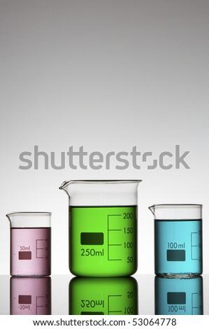 three beakers with colored liquid bright white background - stock photo