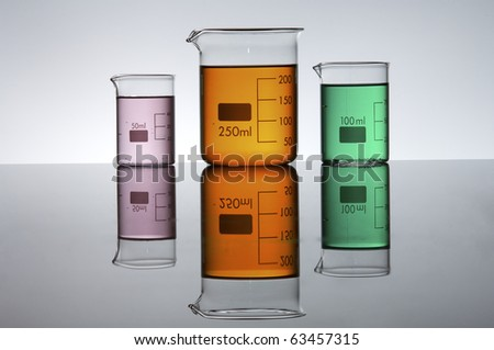 three beakers with colored liquid bright white background - stock photo