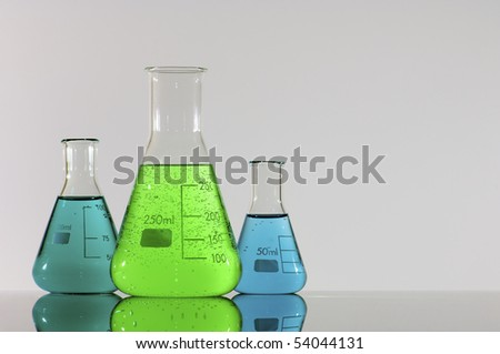 three beakers with green and blue liquid - stock photo