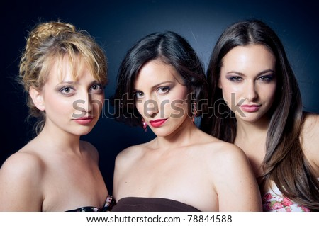 Three beautiful and confident young women on dark background - stock photo