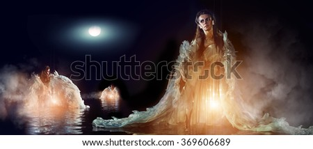 Three beautiful angels in the sea are bathing in the moon rays - stock photo