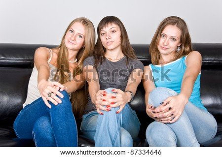 three beautiful attractive girls sitting on the couch and gossip, three friends discuss the article in the magazine, the three friends on the couch talking, laughing girl - stock photo