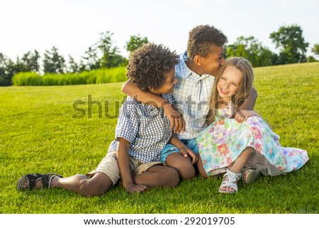 Three beautiful children are playing on the sunny glade with a smile and have fun.