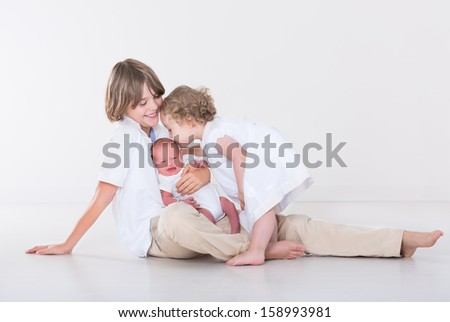 Three beautiful children playing together in a white studio wearing white clothes, school age boy, his toddler sister and a newborn baby boy - stock photo