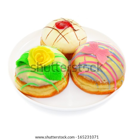 Three beautiful donut with white chocolate. Decorated with a rose and a butterfly.