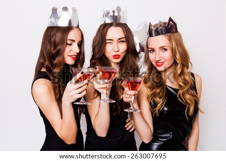 Three beautiful  elegant women celebrate hen-party and drinking  cocktails.  Best friends wearing black  evening dress ,crown  on head and clink glasses. Bright make up, red lips. Inside. - stock photo