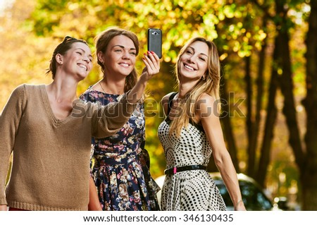 three beautiful friends having fun outdoor in autumn on the street. Outdoors, lifestyle. - stock photo