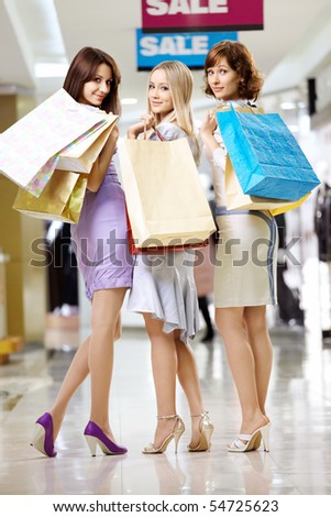 Three beautiful girlfriends in shop with bags - stock photo