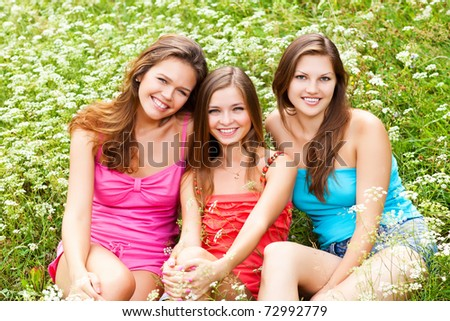 three beautiful girlfriends sitting down on the grass - stock photo