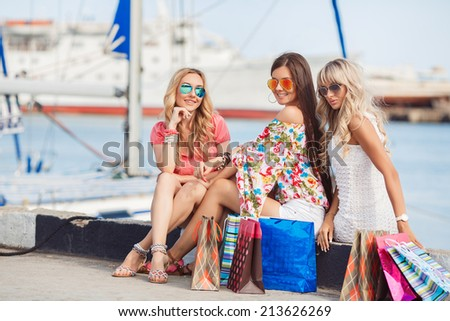 Three beautiful girlfriends with with Shopping Bags. Three beautiful young woman sitting on bench  in the city - stock photo