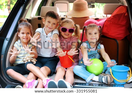 Three beautiful girls and boy sit on a car trunk and laughing