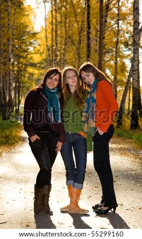 Three beautiful girls are standing and embracing on the path in park - stock photo