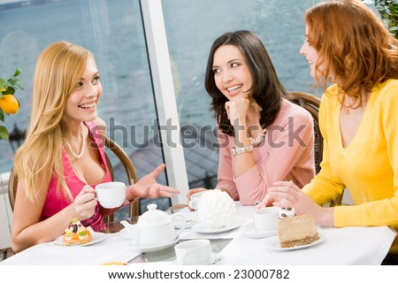 Three beautiful girls gathered together in the cafe