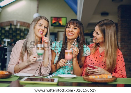 Three beautiful girls in cafes new gadgets are photographed and show photo
