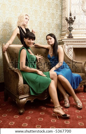 Three beautiful girls in luxury decorated room (toned in sepia) - stock photo