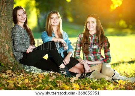 Three beautiful girls laughing together and lying on grass outdoors in a park