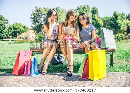 Three beautiful girls looking down at tablet - Women shopping online on a portable computer device - Best friends sitting outdoors and having pause from compulsive shopping - stock photo