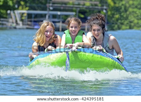 Three beautiful girls on a tube behind a boat.