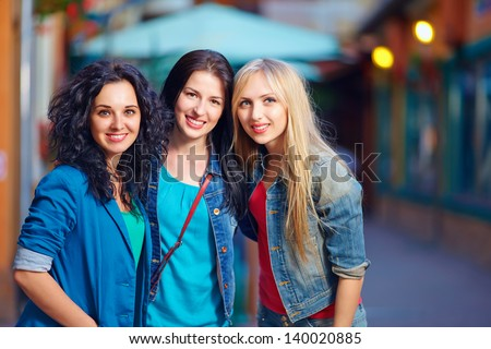 three beautiful girls on evening street - stock photo