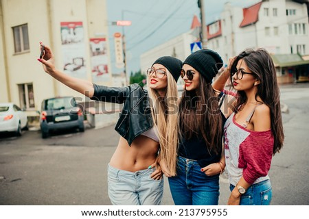 three beautiful girls rest on the street - stock photo
