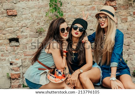 three beautiful girls rest on the street - stock photo