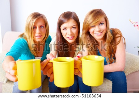 Three beautiful girls sitting on sofa in home with yellow cups - stock photo