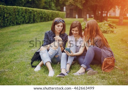 three beautiful girls walking in the park and take pictures on your phone
