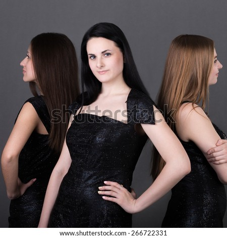 Three beautiful girls with different types of appearances and beauty: brunette, blond and brown-haired models with long straight hair in evening prom outfit, posing back to back - stock photo