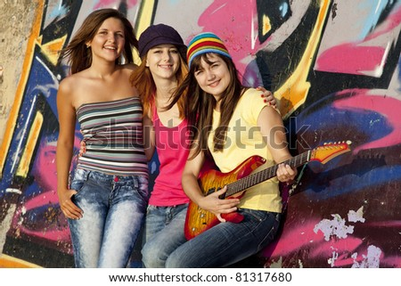 Three beautiful girls with guitar and graffiti wall at background.