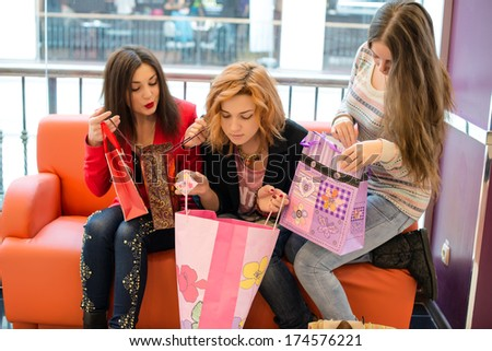 Three beautiful girls with shopping bags in shop - stock photo