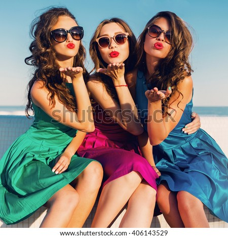 Three  beautiful   glamour  girls  in same colorful dresses posing near the beach, wearing stylish sunglasses and enjoying vacation in summer city. Bright colors. Casual outfit. Send kiss.  - stock photo