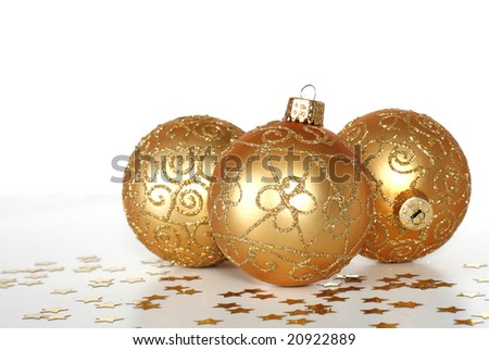 three beautiful gold ornaments with star confetti on white background, copy space - stock photo