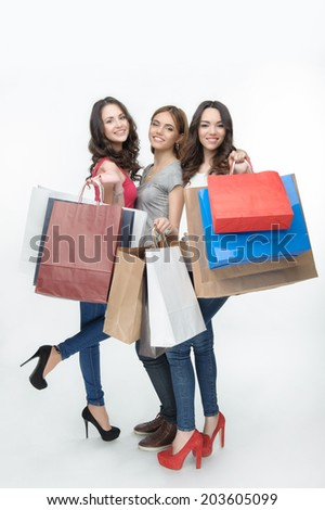 Three beautiful happy girls coming from the department store with many different colorful packages. Isolated on the white background - stock photo