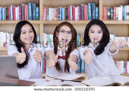 Three beautiful high school students with long hair, showing thumbs up on the camera in the library - stock photo