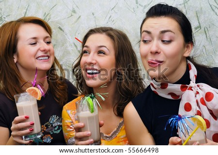 Three beautiful joyful young girls drink cocktails with fruits - stock photo