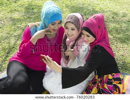 three beautiful muslim girls  take a picture with phone - stock photo