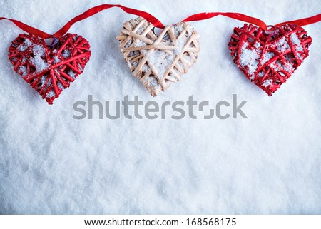 Three beautiful romantic vintage hearts are hanging on a red band on a white snow background. Love and St. Valentines Day concept. - stock photo