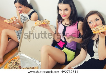 Three beautiful smiling happy fashionable girls eating pizza after partying and night out.