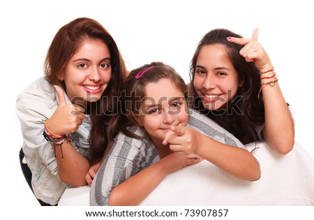 Three beautiful teenagers pointing their hands to different places