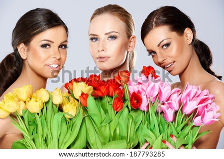 Three beautiful topless women with bunches of fresh spring tulips held to their chests smiling at the camera, head and shoulders portrait - stock photo