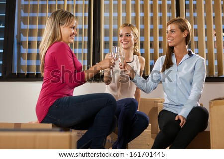 Three beautiful woman are sitting on boxes while celebrating their new business start